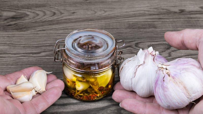 Uitstekende glaskruik en handen met garlics Sativum Alium stock foto