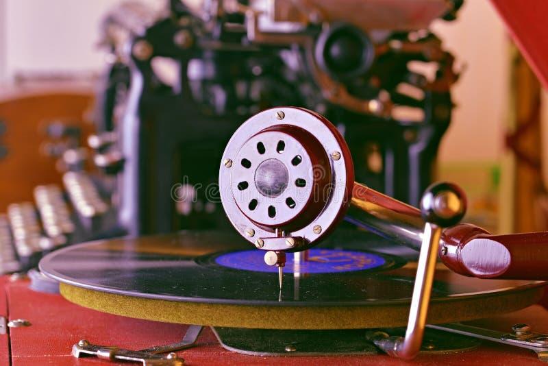 Uitstekende grammofoon met een vinylverslag op houten lijst Uitstekende schrijfmachine op achtergrond stock afbeeldingen