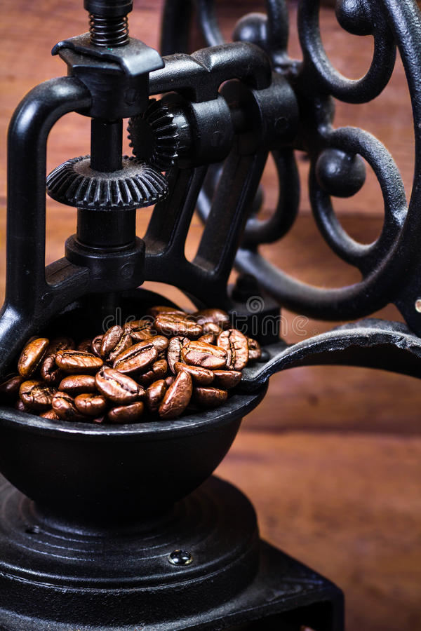 Uitstekende handkoffiemolen met koffiebonen op houten bruin royalty-vrije stock afbeeldingen