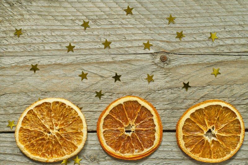Uitstekende houten achtergrond met Kerstmiskroon - droge oranje plakken en gouden confettien in shap van ster Hoogste mening met  stock afbeelding