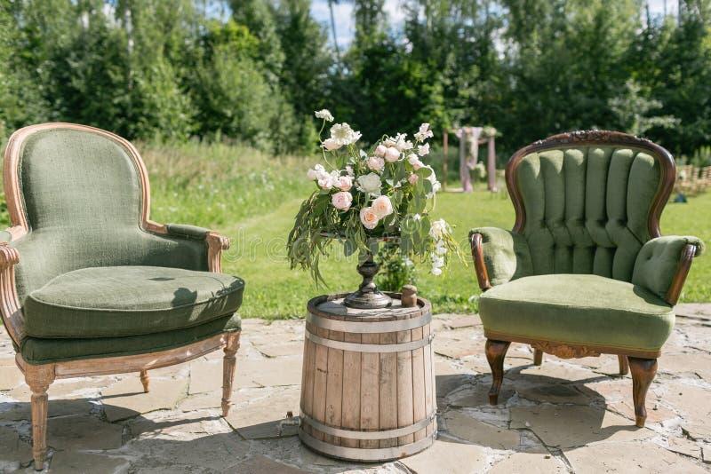 Uitstekende houten stoelen en lijst met bloemdecoratie in tuin openlucht royalty-vrije stock afbeelding