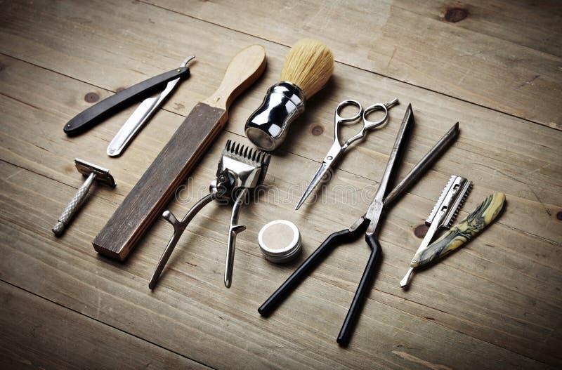 Uitstekende hulpmiddelen van kapperswinkel op houten bureau stock afbeeldingen