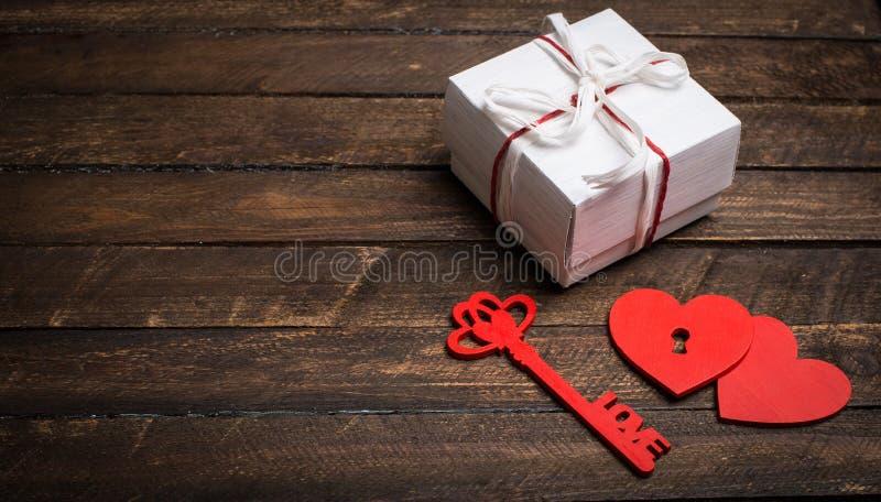 Uitstekende kaart met rode harten, sleutel en giftdoos op oud hout vale royalty-vrije stock fotografie
