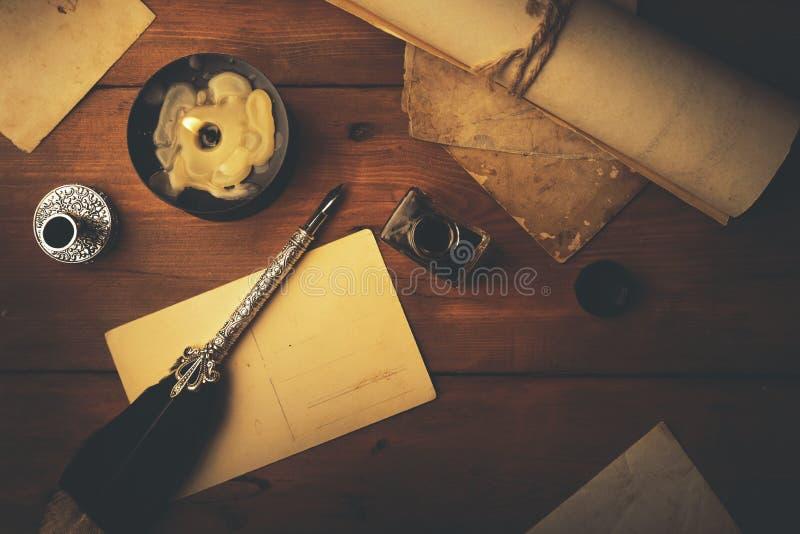 Uitstekende kantoorbehoeften op houten lijst in kaarslicht stock foto's