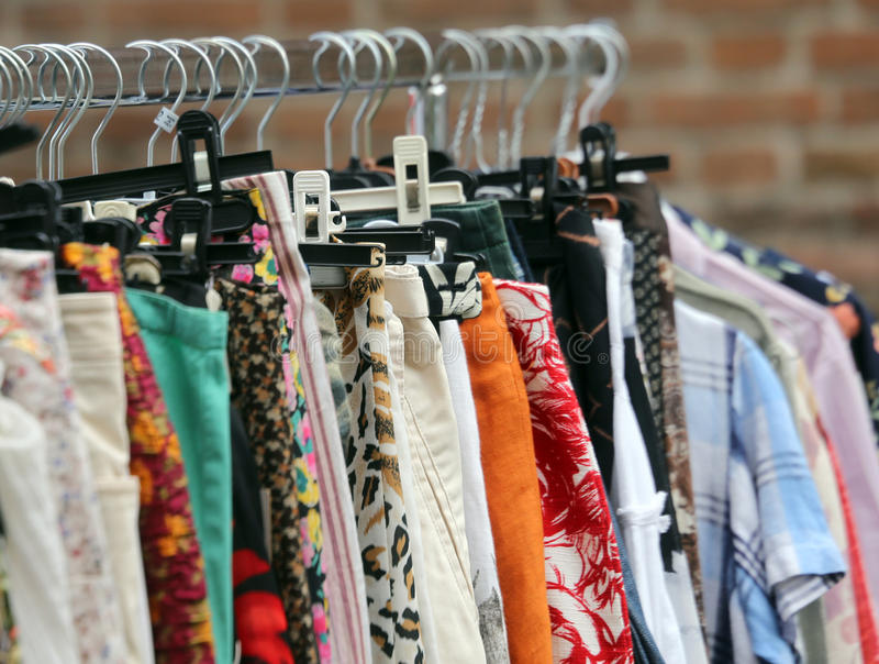 Uitstekende kleren die in de openluchtmarkt van gebruikte dingen hangen stock fotografie