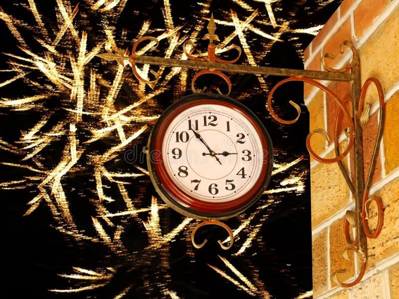 Uitstekende klok en gele bakstenen muur op gouden vuurwerkachtergrond royalty-vrije stock afbeeldingen