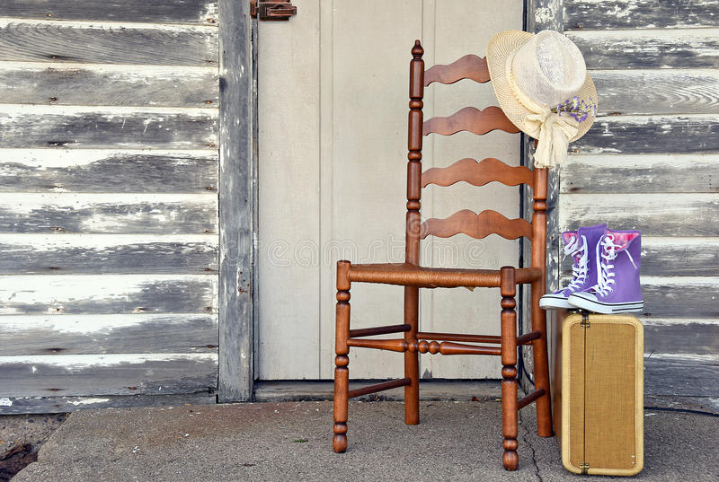 Uitstekende koffer met stoel door houten oude deur stock foto