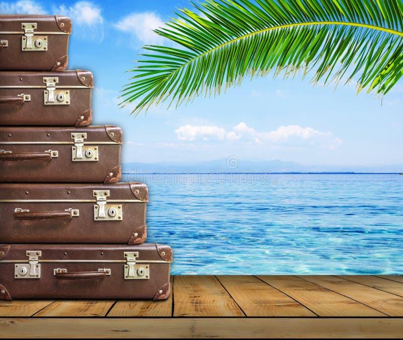 Uitstekende koffer op houten raad op overzeese en palmachtergrond royalty-vrije stock fotografie