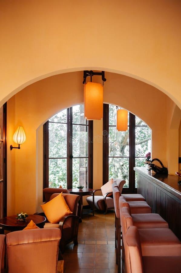 Uitstekende koloniale bar met leunstoel, klassieke lampen en barkrukken stock afbeeldingen