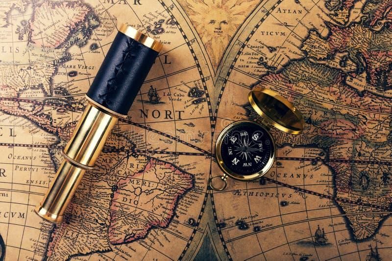 Uitstekende kompas en kijker op oude wereldkaart royalty-vrije stock foto's