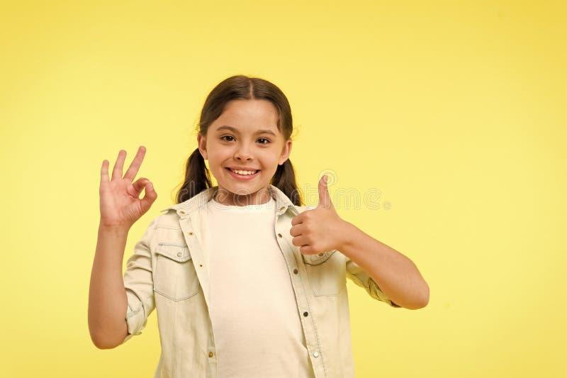 Uitstekende kwaliteit Het jong geitjemeisje toont duim en o.k. gebaar gele achtergrond Het kind adviseert hoogst uitstekende kwal royalty-vrije stock foto