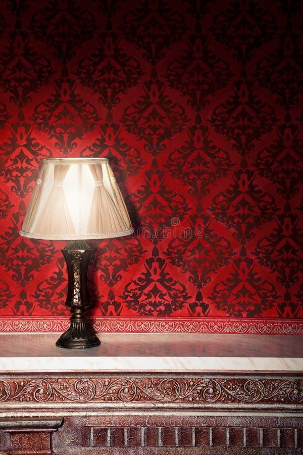 Uitstekende lamp op oude open haard in ruimte met rood roccopatroon stock foto