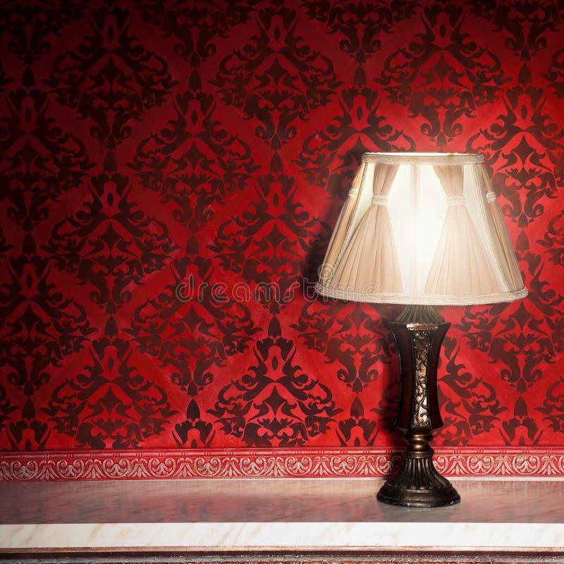 Uitstekende lamp op oude open haard in ruimte met rood roccopatroon royalty-vrije stock foto's