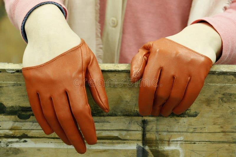 Uitstekende leerhandschoenen Vrouwen` s handen die bruine roodachtige uitstekende handschoenen dragen De elegantie en de luim zie royalty-vrije stock afbeeldingen