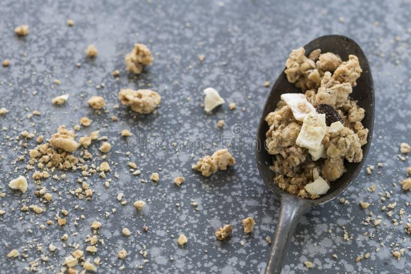 Uitstekende lepel met granola, muesli, tegen concrete achtergrond royalty-vrije stock foto