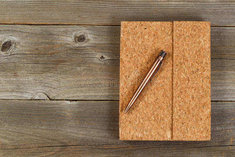 Uitstekende metaalpen en cork behandelde blocnote op rustiek houten bureau royalty-vrije stock afbeeldingen
