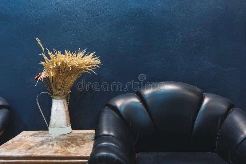 Uitstekende meubilair en decoratie, Donkerblauwe muur met een deel van uitstekende leerleunstoel en vaas met bloemen op zijlijst stock fotografie