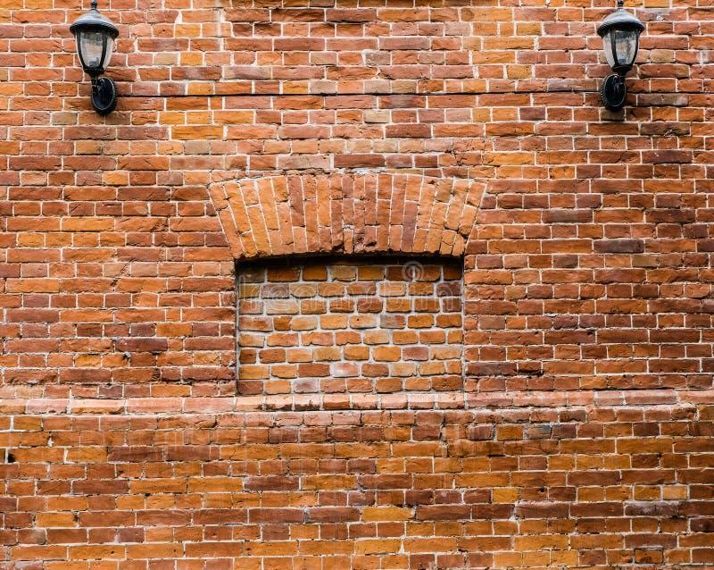 Uitstekende muurlamp op een rood-oranje en bruine muur van oude baksteen royalty-vrije stock afbeelding