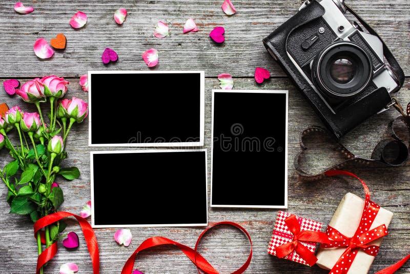 Uitstekende retro camera met lege fotokaders en roze rozen stock afbeeldingen