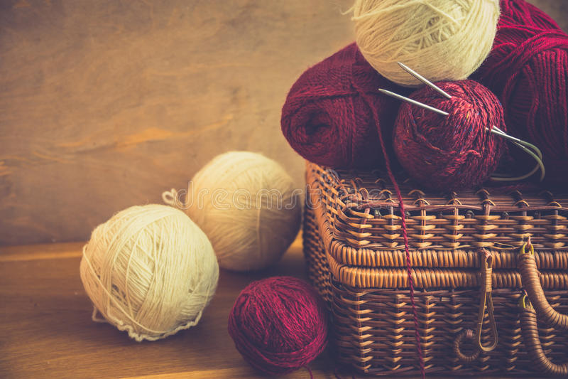 Uitstekende rieten clews van borstbollen van rood wit wolgaren, naalden op houten lijst, het breien, ambachten, hobbyconcept royalty-vrije stock fotografie
