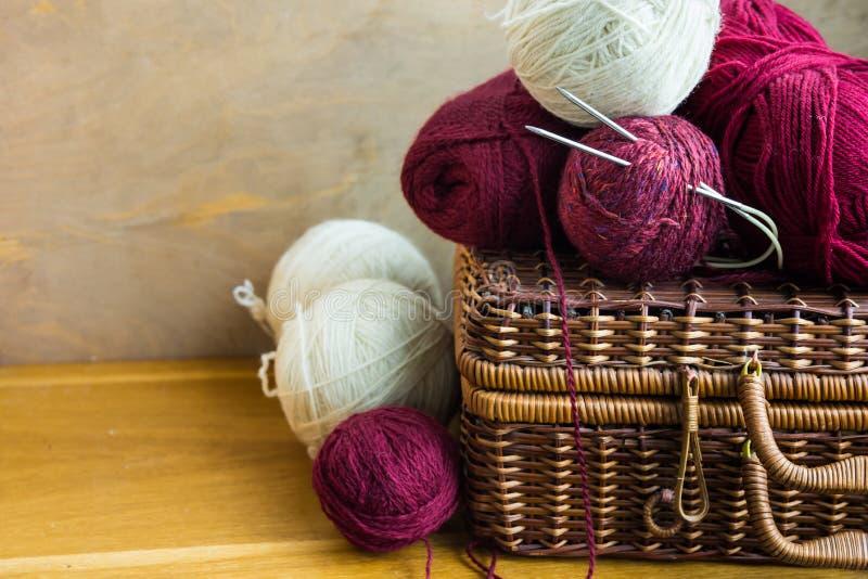 Uitstekende rieten clews van mandballen van rood wit wolgaren, naalden op houten lijst, het breien, ambachten, hobbyconcept stock foto's