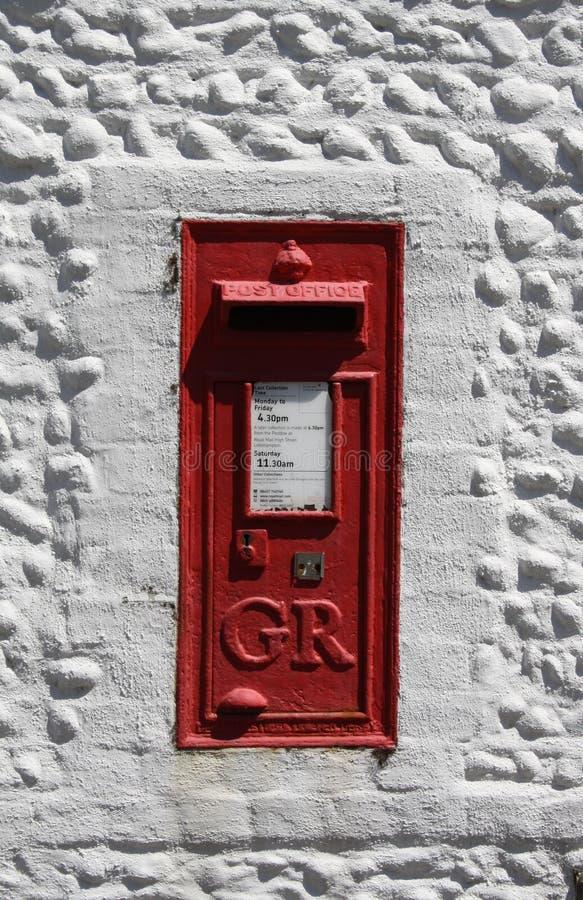 Uitstekende rode Britse die postbox in een witte muur wordt geplaatst stock fotografie