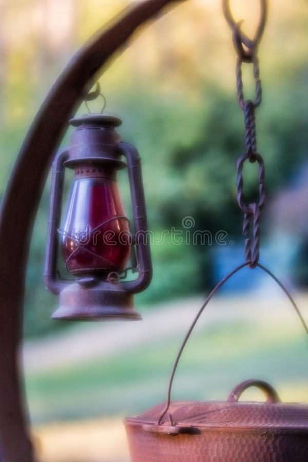 Uitstekende rode lantaarn die op antieke rustieke cowboy kokende post overhandigen royalty-vrije stock foto