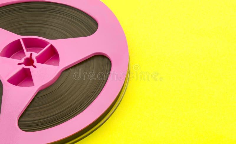 Uitstekende roze audiospoel met opnameband op gele document achtergrond In pop-artstijl stock afbeeldingen