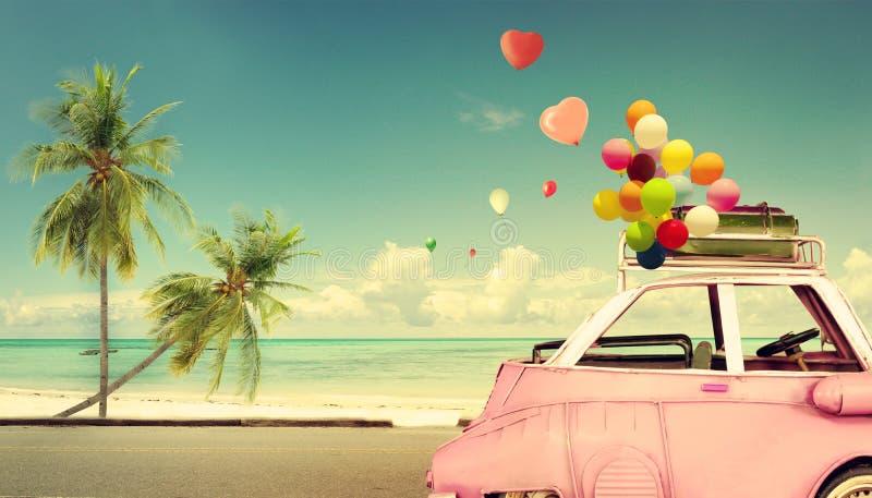 Uitstekende roze klassieke auto met hart kleurrijke ballon op strand blauwe hemel royalty-vrije stock afbeeldingen