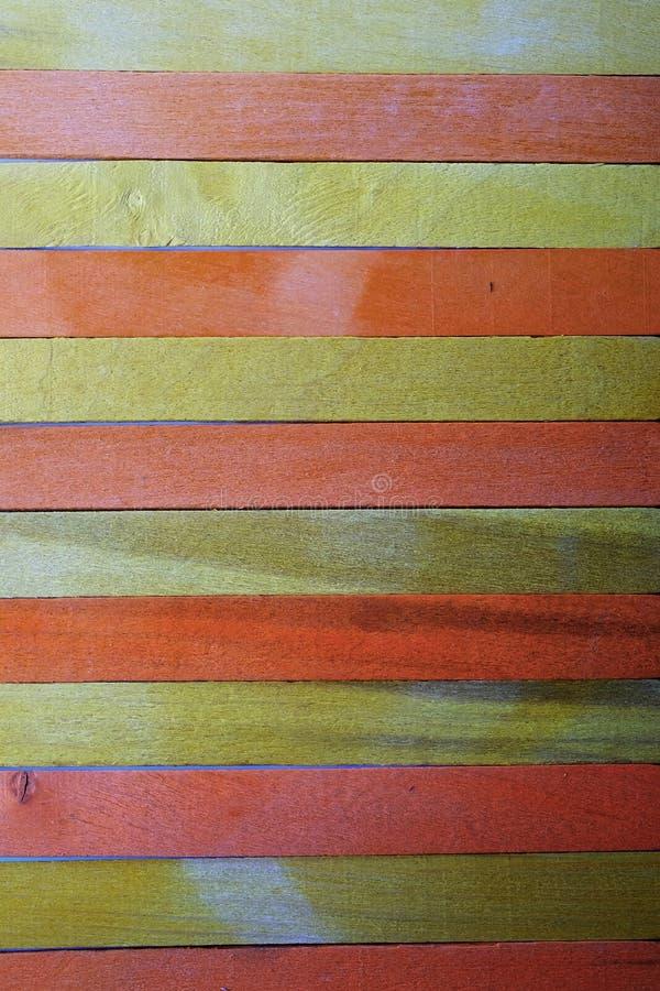 Uitstekende ruwe geel onderbreekt met oranje kleur houten de textuurachtergrond van de verdelingsmuur stock foto