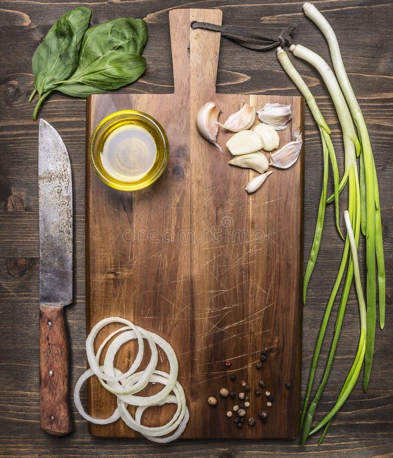 Uitstekende scherpe raad met ingrediënten voor het koken, knoflook, uiringen, groene het messenplaats van de uienolie voor tekst, stock fotografie