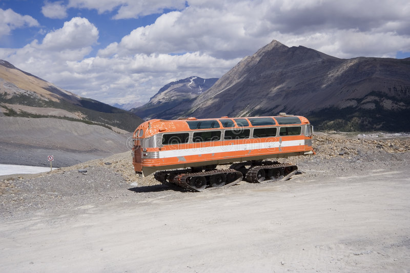 Uitstekende sneeuwscooter in de rotsachtige bergen stock foto