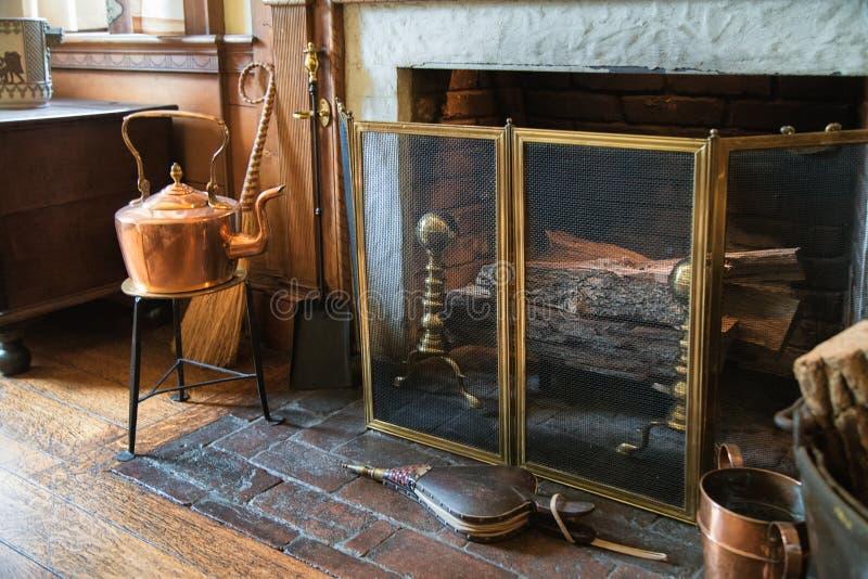 Uitstekende steenopen haard met metaalhulpmiddelen en brandhout stock foto