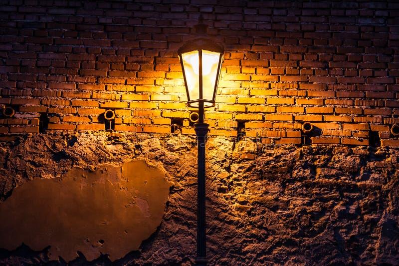 Uitstekende straatlantaarn tegen een bakstenen muur bij nacht stock afbeeldingen