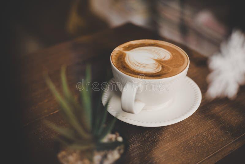 Uitstekende toon van hete koffie latte kunst in hartvorm in kop op Ta stock foto's