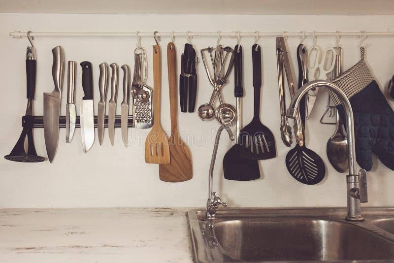 Uitstekende toon van Keuken kokende werktuigen op rek stock afbeelding