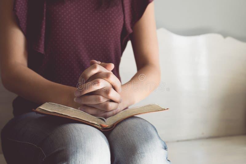 Uitstekende toon van vrouwenhanden op bijbel zij leest en bidt stock afbeeldingen