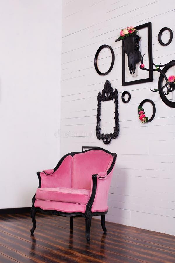 Uitstekende velorleunstoel, in een heldere ruimte Diverse lege omlijstingen met een schedel en geweitakken die op een houten muur royalty-vrije stock afbeelding