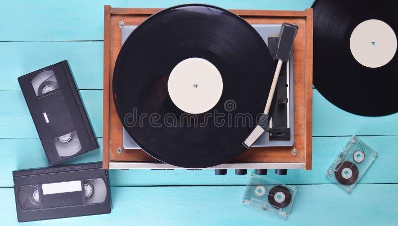 Uitstekende vinylspeler met platen, videocassette, audiocassette op een blauwe houten achtergrond Hoogste mening Retro media tech royalty-vrije stock fotografie