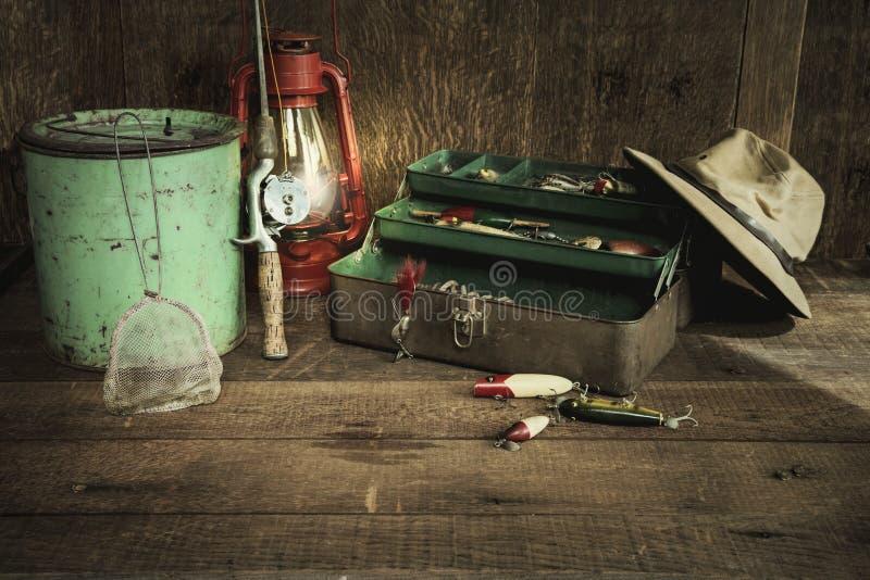 Uitstekende vistuigen en lantaarn op grungy houten oppervlakte royalty-vrije stock afbeelding