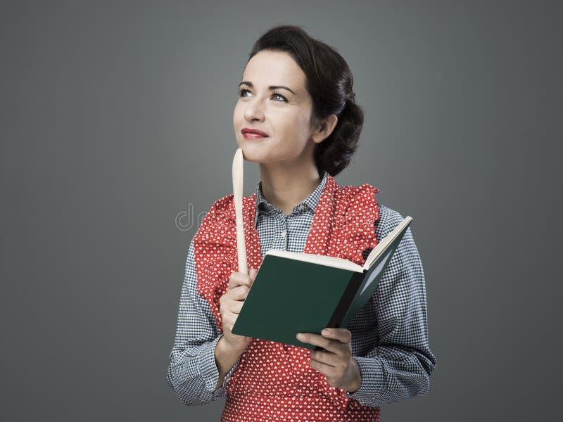 Uitstekende vrouw met kookboek stock afbeeldingen