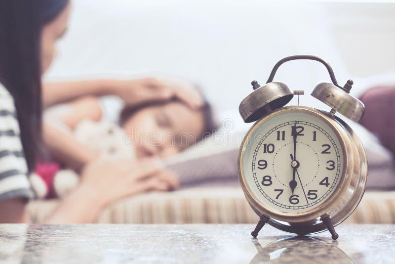 Uitstekende wekker op achtergrond die van moeder zorgkind nemen stock fotografie