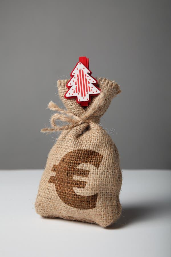 Uitstekende zak met geld, euro teken en nieuw jaar en Kerstmisboom stock afbeelding