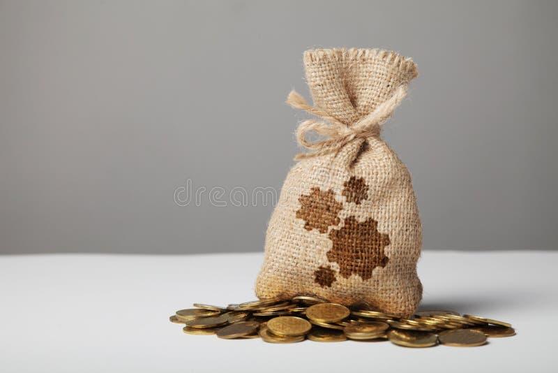 Uitstekende zak met geld op gouden muntstukken Toestellensymbool, gevestigde voordelige zaken stock fotografie