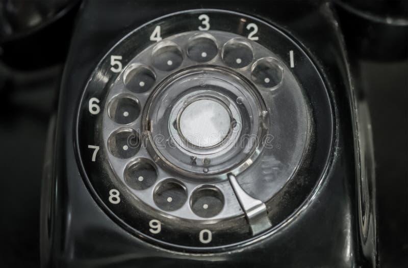 Uitstekende zwarte wijzerplaattelefoon, mededeling stock fotografie