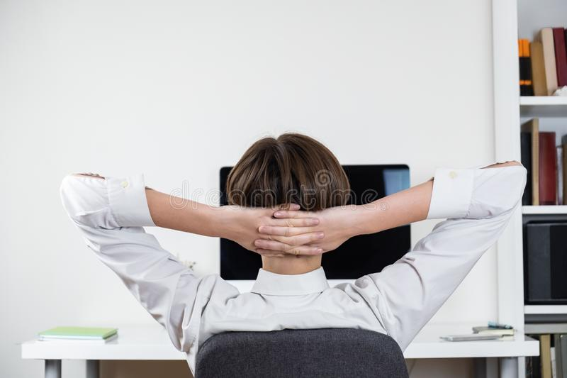 Uitstelconcept: beambte het uitrekken zich voor het zwarte computerscherm royalty-vrije stock afbeeldingen