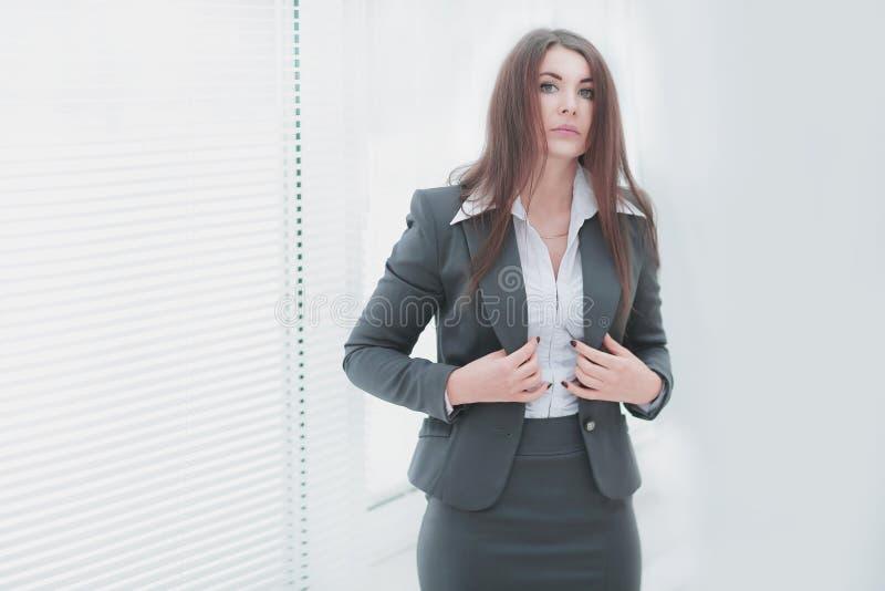 Uitvoerende bedrijfsvrouw die zich dichtbij venster in ruim bureau bevinden royalty-vrije stock foto's