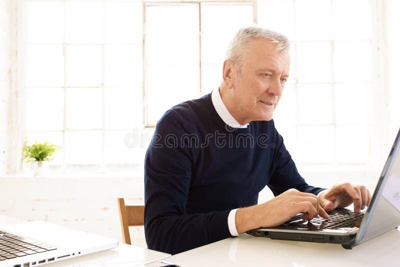 Uitvoerende bejaarde zakenman die aan laptop in het bureau werken royalty-vrije stock fotografie