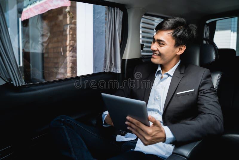 Uitvoerende gebruikende tablet terwijl in de auto op zijn manier aan het bureau royalty-vrije stock afbeelding