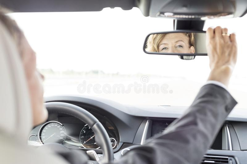 Uitvoerende het aanpassen achteruitkijkspiegel drijfauto tijdens zakenreis royalty-vrije stock foto